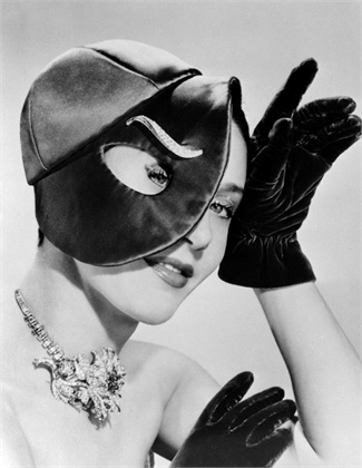 12 Nov 1949, Paris, France --- Original caption: Schiaparelli, in a surrealistic mood, designs this red satin, visored evening cap with an elongated peephole for the eye. A diamond clip from Van Cleef & Arpels makes a weird eyebrow. --- Image by © Bettmann/CORBIS